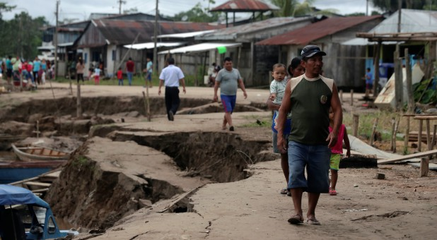 Residents walk in an area affected by a quake in Puerto Santa Gema, on the outskirts of Yurimaguas, in the Amazon region, Peru.