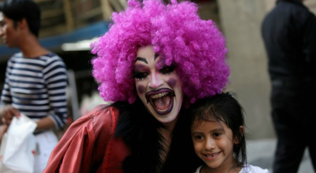 "A participant dressed in drag poses for a picture with a child during the ""Drag Queen Story Hour"" event."