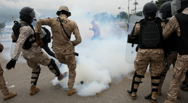 Haitian National Police (PNH) officers kick a tear gas canister during a protest outside of the Legislative Palace in Port-au-Prince.