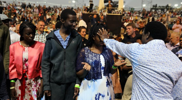 T.B. Joshua, a Nigerian evangelical preacher, places his hand over the face of a woman as he leads a religious retreat on Mount Precipice, Nazareth, northern Israel.