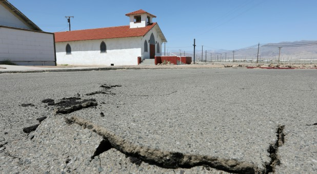 Cracks are seen in the street next to Trona Community Church after a powerful magnitude 7.1 earthquake broke, triggered by a 6.4 the previous day, near the epicenter in Trona.