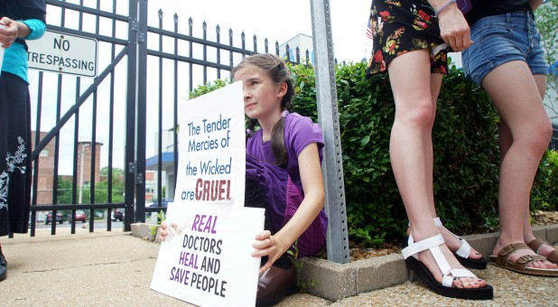A young anti-abortion rights activist sits behind her signs at a rally in front of the Planned Parenthood in St. Louis, Missouri.